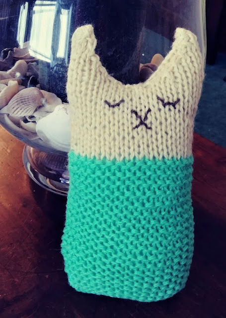 super simple and easy to knit stuffed cat with embroidered face.