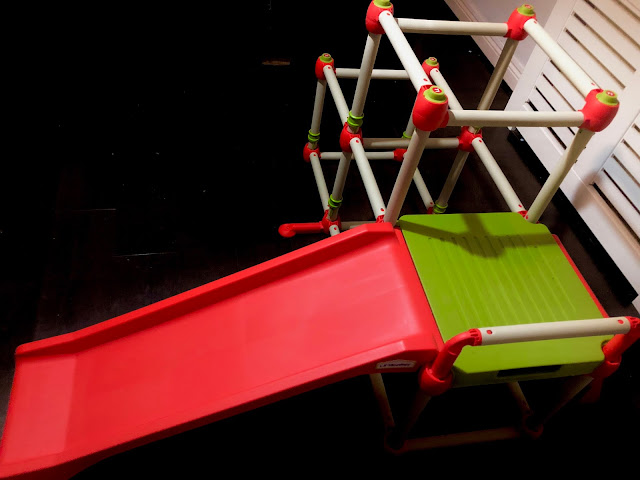 A white, green and red climbing frame with a red slide