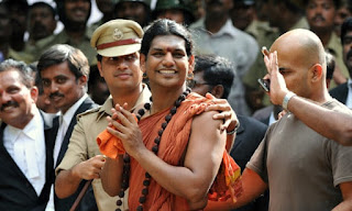 Police escort Hindu 'godman' Nithyananda to a bail hearing in 2012. Photograph: Manjunath Kiran/AFP via Getty Images