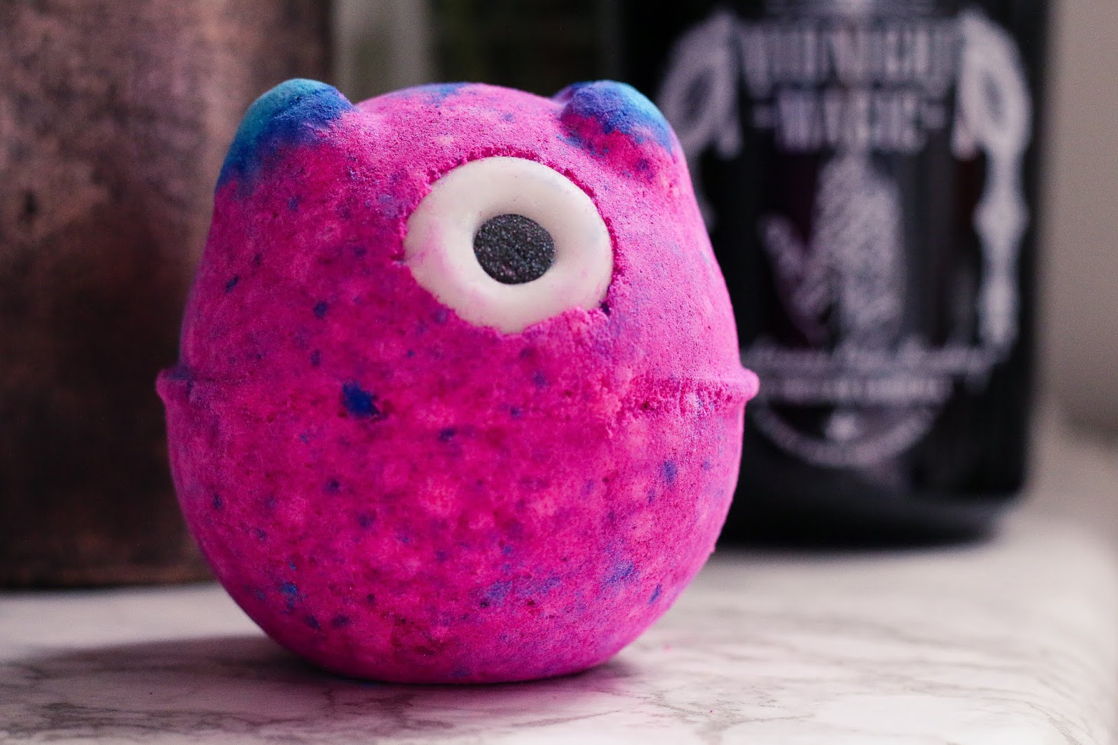 Close up photo of Monsters' Ball Lush bath bomb. Pink bath bomb with specs of blue throughout and one giant eye in the centre - On thelifeofaglasgowgirl.co.uk