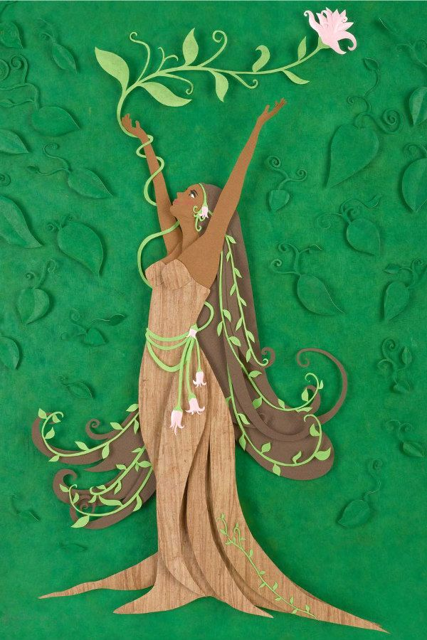 paper sculpture of tree woman with arms raised and flowing hair as branches