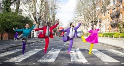 Περιγραφή: δύο άντρες και δύο γυναίκες, φορώντας ρούχα με πολύ έντονα χρώματα, χορεύουν περνώντας μια διάβαση.