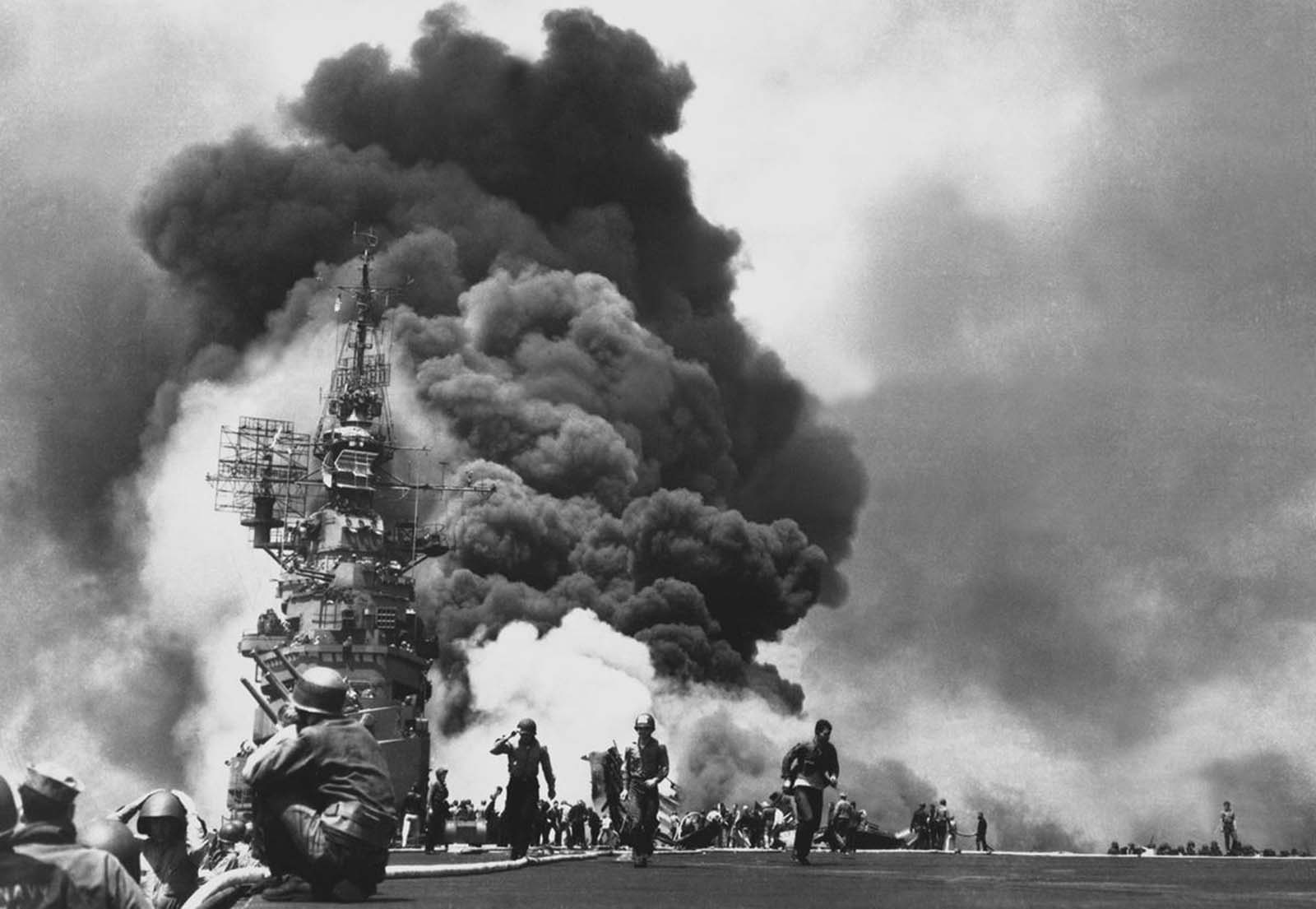 Flames leap from the deck of the USS Bunker Hill, after it was hit by two Kamikazes in 30 seconds on May 11, 1945 off Kyushu. 346 aboard were killed, another 264 wounded.