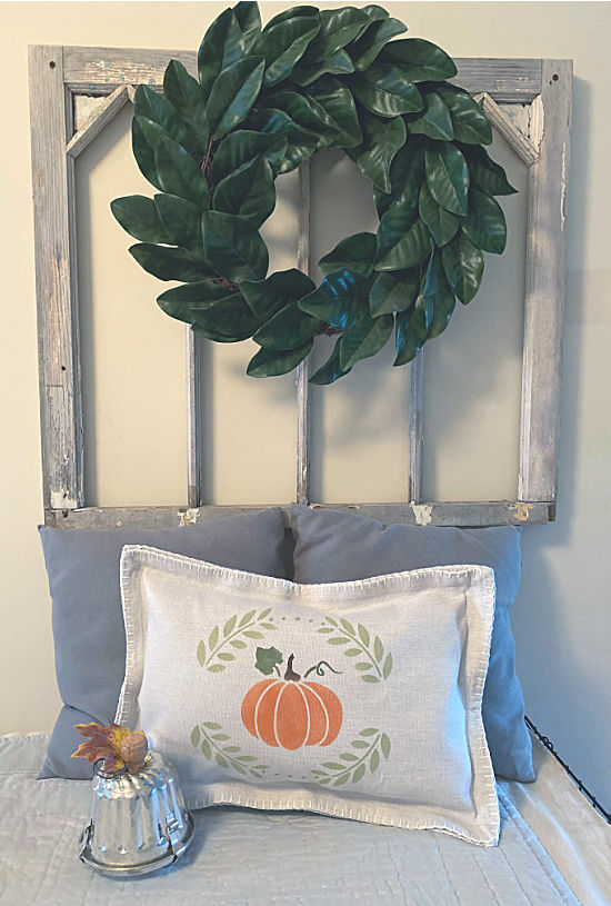 stenciled pumpkin pillow and vintage window with wreath