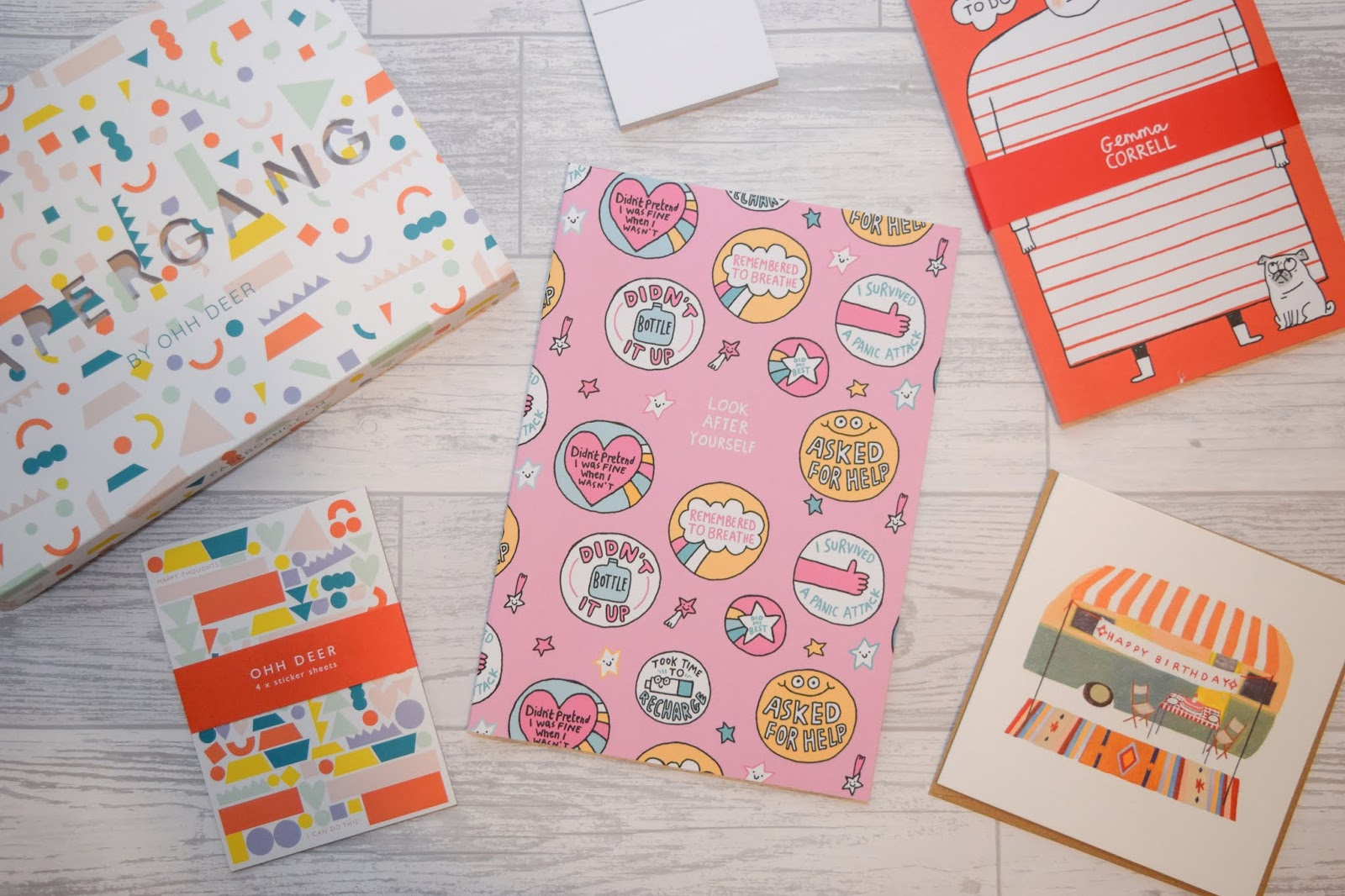An overview of the contents of a stationery box including post it notes, an A4 notebook, an A5 list pad, a birthday card and some stickers.