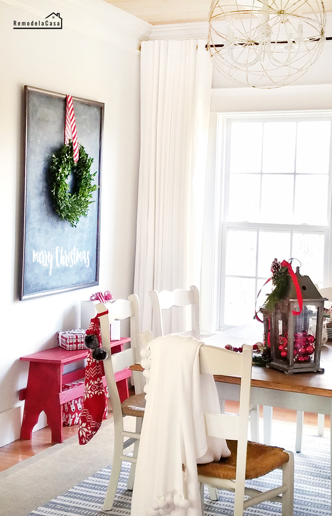 dining room decorated for Christmas with chalkboard and red bench.