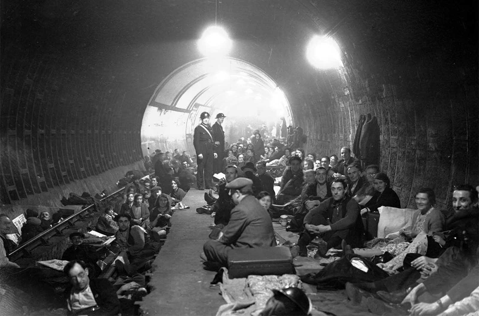 People shelter and sleep on the platform and on the train tracks, in Aldwych Underground Station, London, after sirens sounded to warn of German bombing raids, on October 8, 1940.