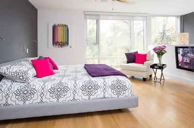 Cool bright color bedroom design features gray bed with pink pillows and purple blanket also beige chair with pink and purple cushions