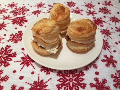 Three puff pastry mince pies filled with whipped cream on a plate with a Christmas tea towel