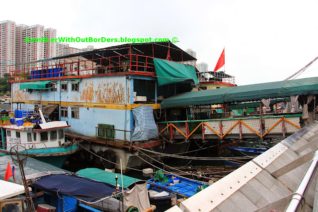 A Tanka houseboat that's docked next to the shore with a connecting walkway, Aberdeen Promenade, Hong Kong