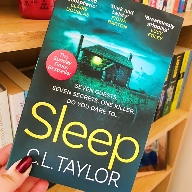 the book sleep by c.l. taylor held up in front of bookshelf
