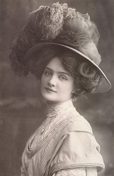 Retrato en blanco y negro de señora llevando sombrero de la época con plumas