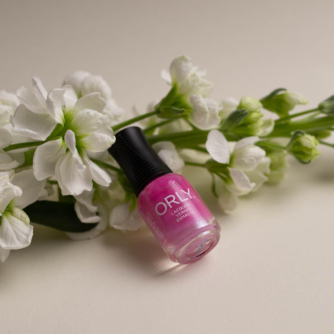 """Vaalean alustan päällä pitkä valkea kukka, jonka päälle kynsilakka purkki on """"kaatunut"""""""