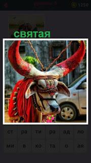 стоит святая корова в цветном одеянии с большими рогами