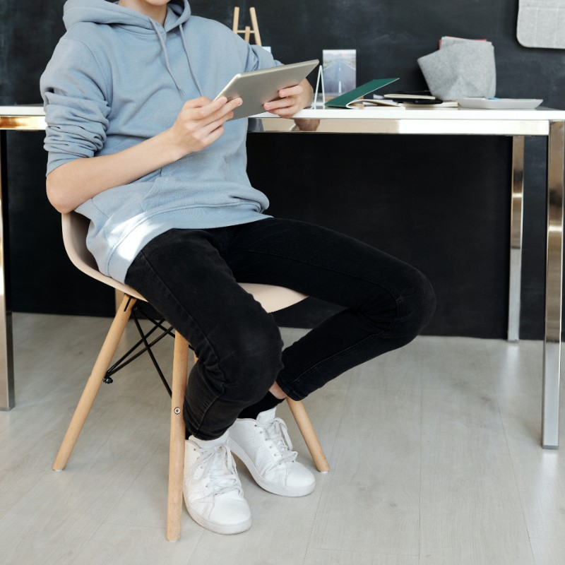 A teenage guy sitting on a chair, operating mobile phone.