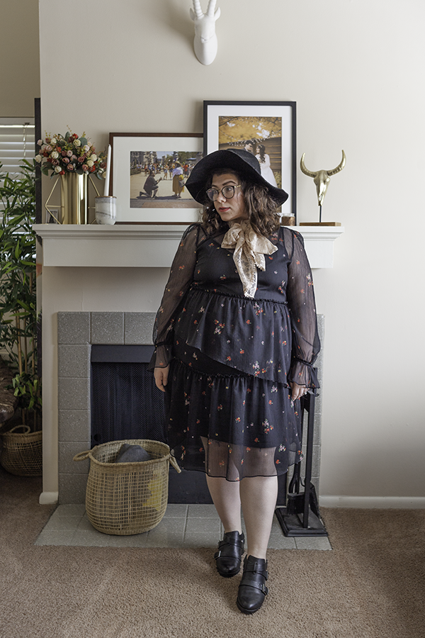 An outfit consisting of an oversized black floppy hat, a pastel pink lace scarf tied in a bow around the neck, a black long sleeve sheer dress with red, yellow and pink microfloral motif, and black buckle ankle booties.