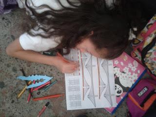 niña pinta moldes de estructuras en papel puente broklin