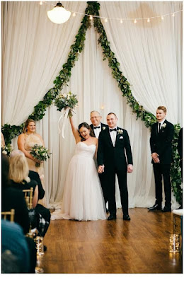 K'Mich Weddings - wedding planning - bride and grooms holding hands in the air after ceremony