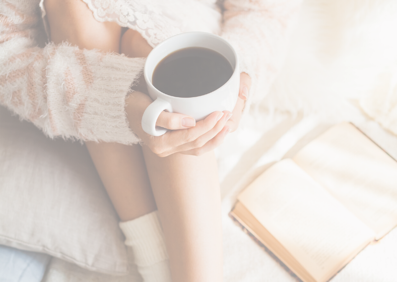 Lady sat on the bed with a book and a coffee in a post about ten easy ideas for your self-care and reset day.