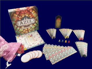 The game components alongside the game box. There is a pink bag with translucent tiles in various colours that resemble small pieces of glass, about the size and shape of starburst candies. There are several round tiles, a scoring board, long rectangular tiles with notched bottoms that come in four sets of eight, and wide rectangular tiles with notches along the top designed for the long pieces to fit into. There are also four plastic pawns and a tall but skinny cardboard box decorated to look like a tower of stained glass windows..