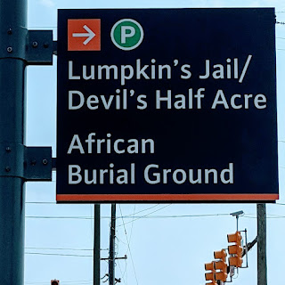 Photo of sign on E. Broad St. near 17th St. directing one to the African Burial Ground and Devil's Half Acre sites.