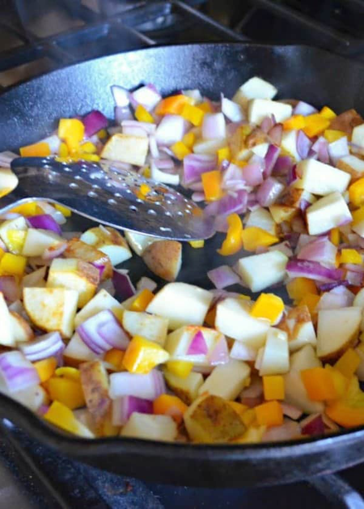 Browning cubed potatoes, onions and bell pepper in a cast iron pan for Breakfast Burritos Recipe.