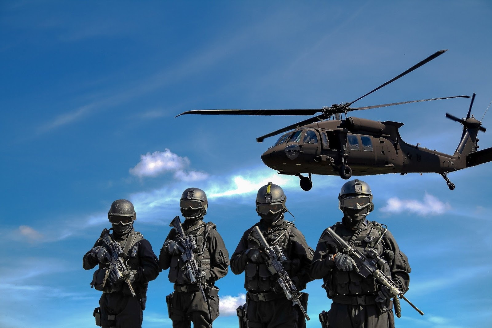 four masked soldiers standing next to each other with a black hawk helicopter flying overhead to illustrate blog post about show inside combat rescue