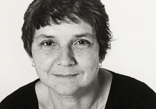 A black and white image of Adrienne Rich looking directly at the camera with a warm expression. She has short salt-and-pepper hair, dark eyes, and freckles. She wears a black top and small, silver, hoop earrings.