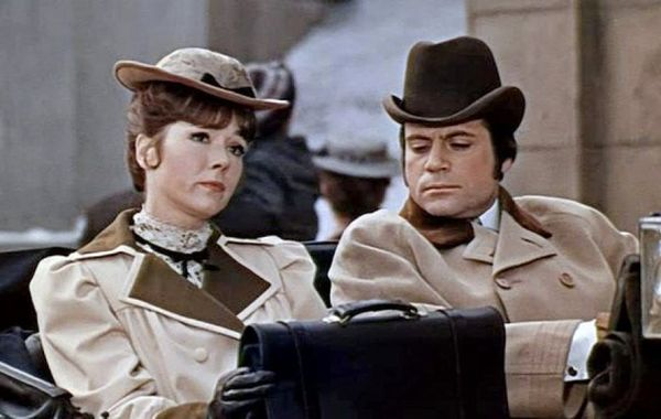 Diana Rigg and Oliver Reed in period dress sitting in a carriage