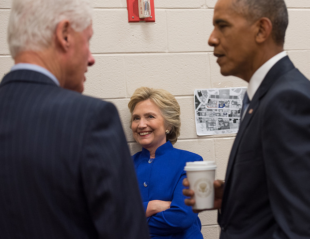 image of Hillary Clinton leaning against a wall backstage at the Democratic convention, she is watching Bill Clinton and Barack Obama standing and talking, and she is grinning