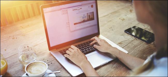 شخص يستخدم Mac في مكان عام لنسيان شبكة Wi-Fi