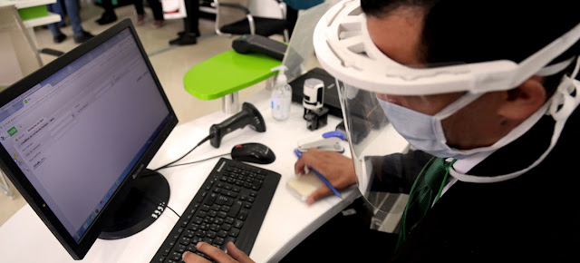Un hombre trabaja con mascarilla y pantalla para protegerse del coronavirus en ArgeliaOIT/Yacine Imadalou