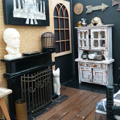 One-twelfth scale miniature scene, with a fireplace, distressed dresser and a bed in it.