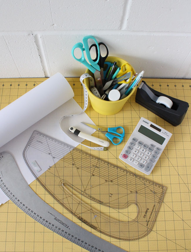 Overhead photo of a yellow cutting mat and pattern making tools