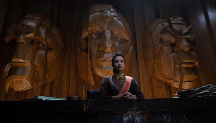 Imagem: um fundo de madeira com três rostos inumanos esculpidos, e na frente, uma personagem interpretada por uma mulher negra, em trajes formais cor bege, com uma gravata vermelha e uma faixa, sentada em um tablado de corte de tribunal de mãos cruzadas olhando para frente.