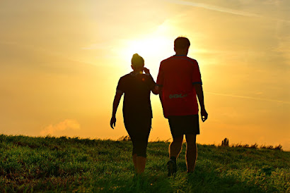 Man and woman walking on a hillside in sunlight