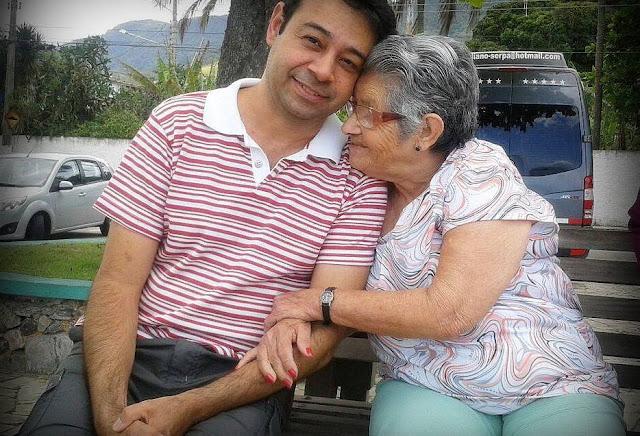 Rapaz sorri abraçado com mulher idosa, em um banco de praça
