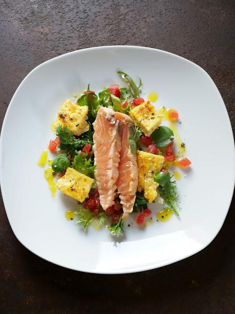 Marinierter Lachs mit kross angebratener Sesam-Polenta auf Blattsalat vom Indischen Senf und Brunnenkresse mit Leindotteröl-Vinaigrette und Tomatenwürfel.