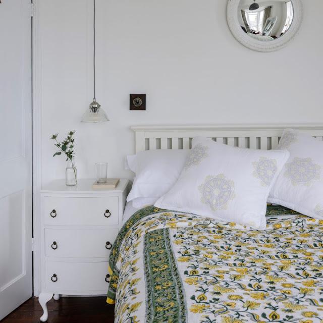 Kamar tidur putih dengan lampu gantung tergantung di atas meja samping