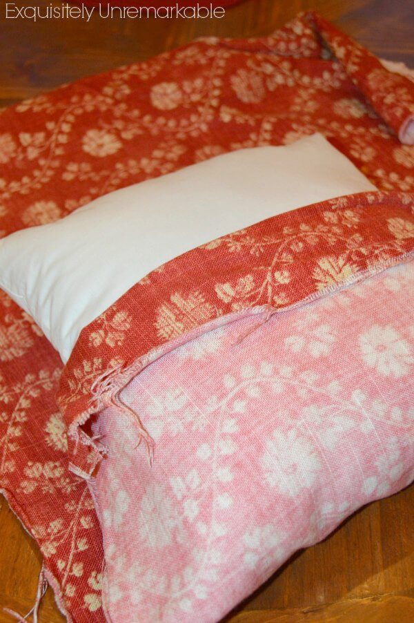 red fabric folded over white square pillow form