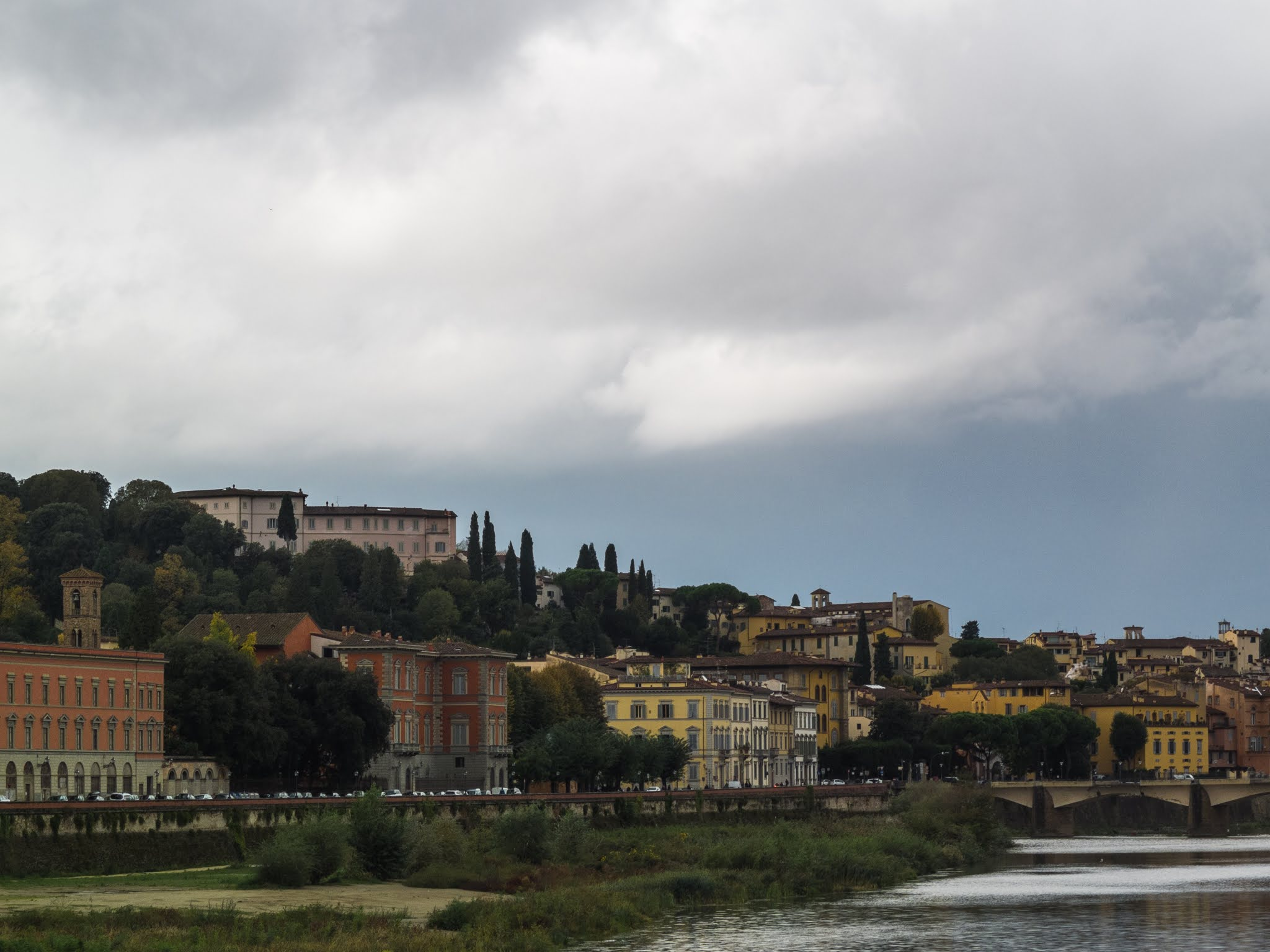 Landscape of Florence on a cloudy day with river Arno in the foreground.