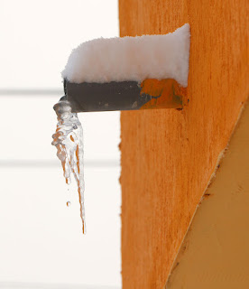 A drip falling from an icicle off the balcony