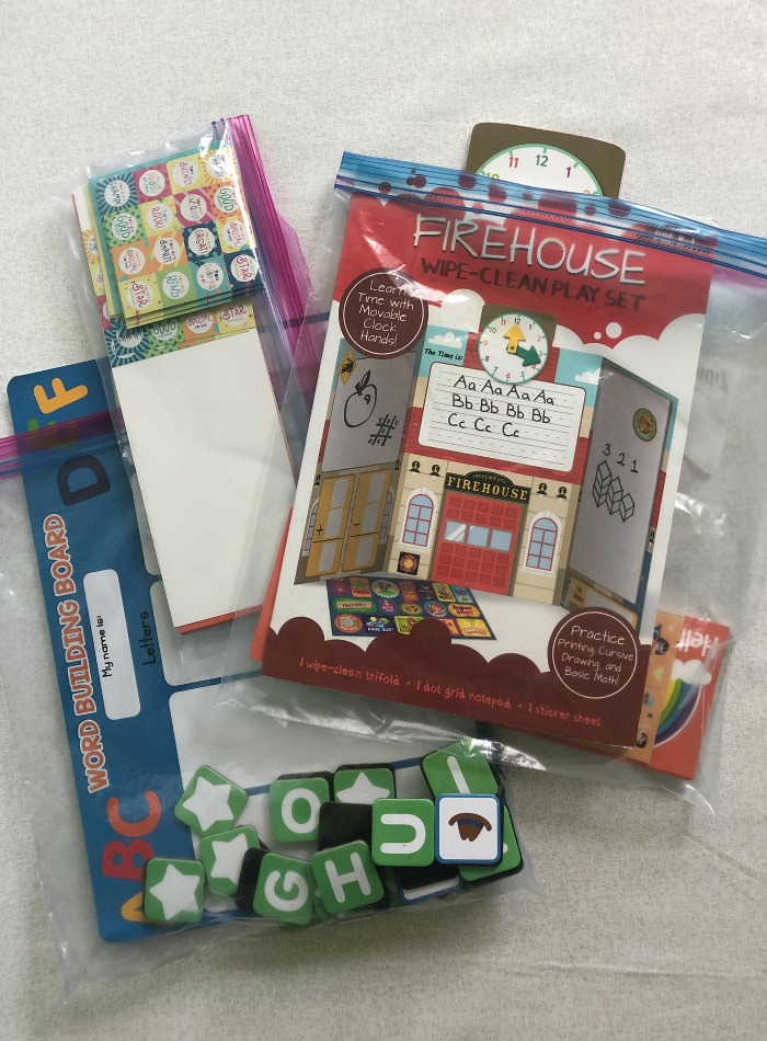 Activity bags for toddlers full of stickers, magnets, a firehouse themed dry erase board all in ziplock bags to hand them on long road trips