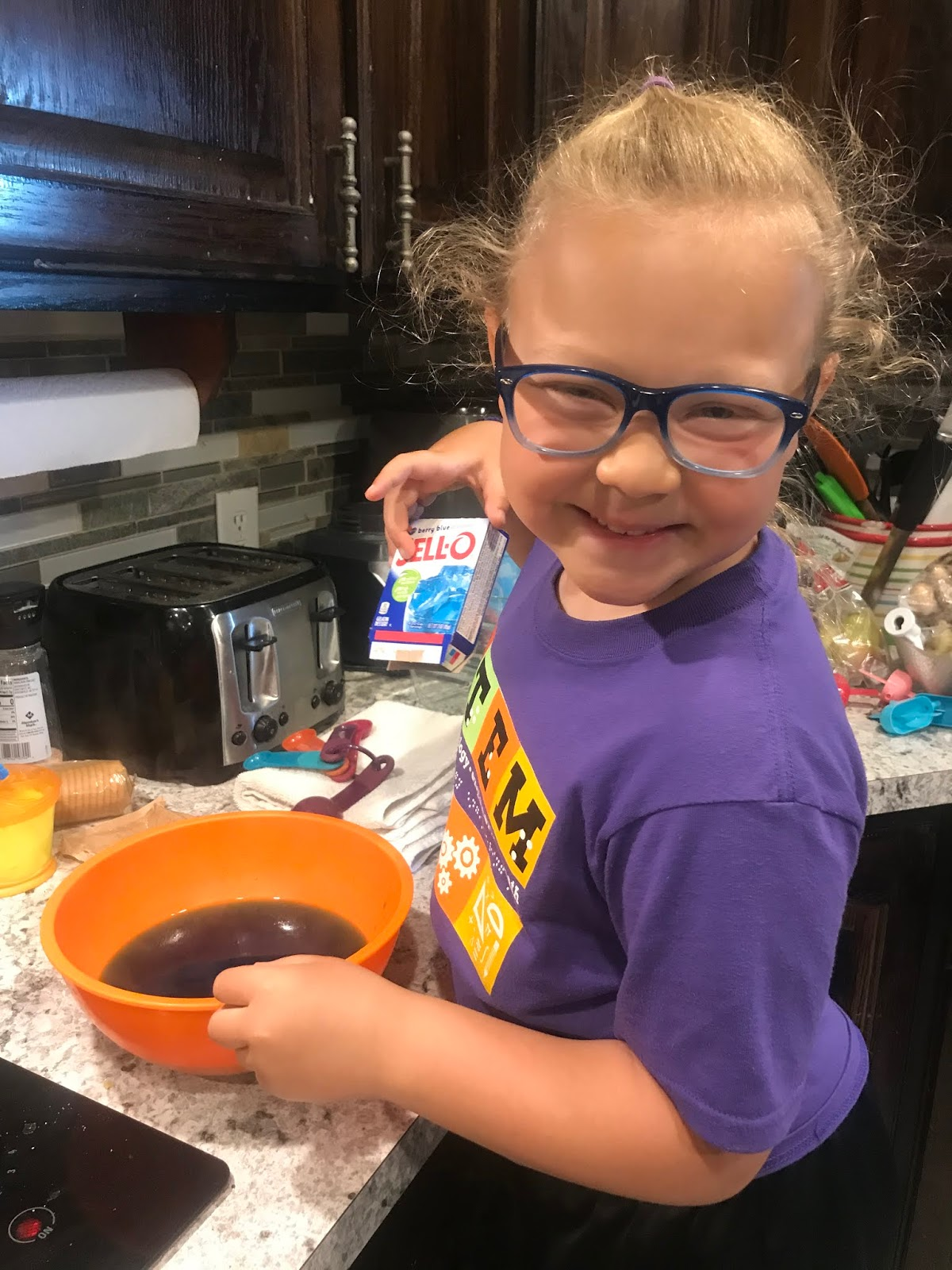a girl smiles and holds a Jell-o box as she mixes ingredients