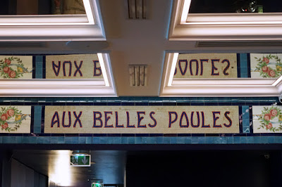 Section of a mosaic frieze saying 'Aux Belles Poules', with rose wreaths at either end of the words, and blue borders; and its reflection in a mirrored ceiling.