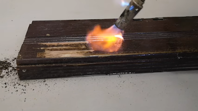 بشبوري لهب يخرج منه نار موجه على قطعة من الخشب و إزالة الدهان