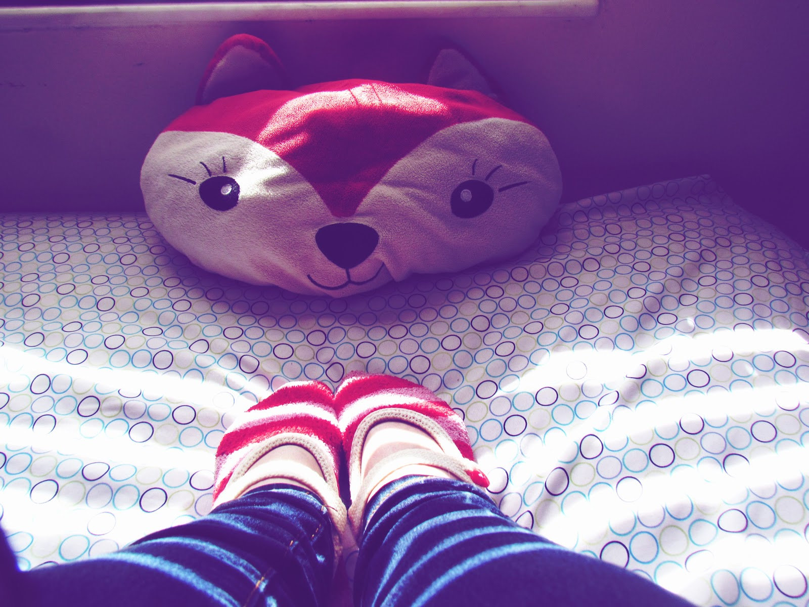 A Fox Pillow and a Woman Wearing Candy Cane Striped Fuzzy Socks for the Winter Months in Florida