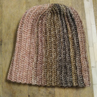 A crocheted beanie with ribbing and color changes from pink to gray to brown.