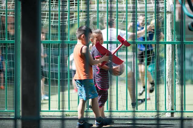 Футбольная площадка, дети с самолетиком и мячом, игра в футбол