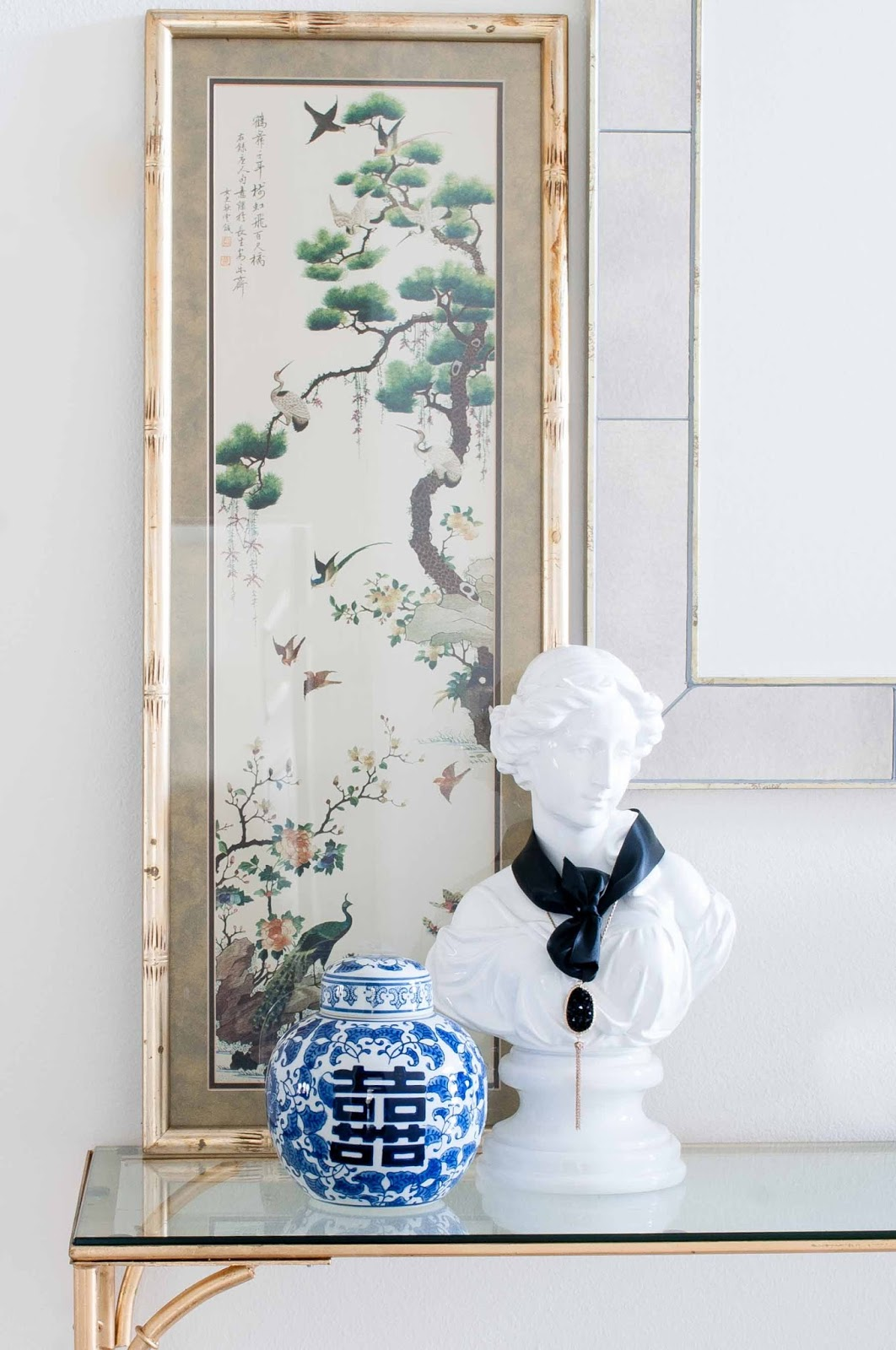 A white bust and ginger jar sit pretty next to a vintage gilt bamboo framed art print.